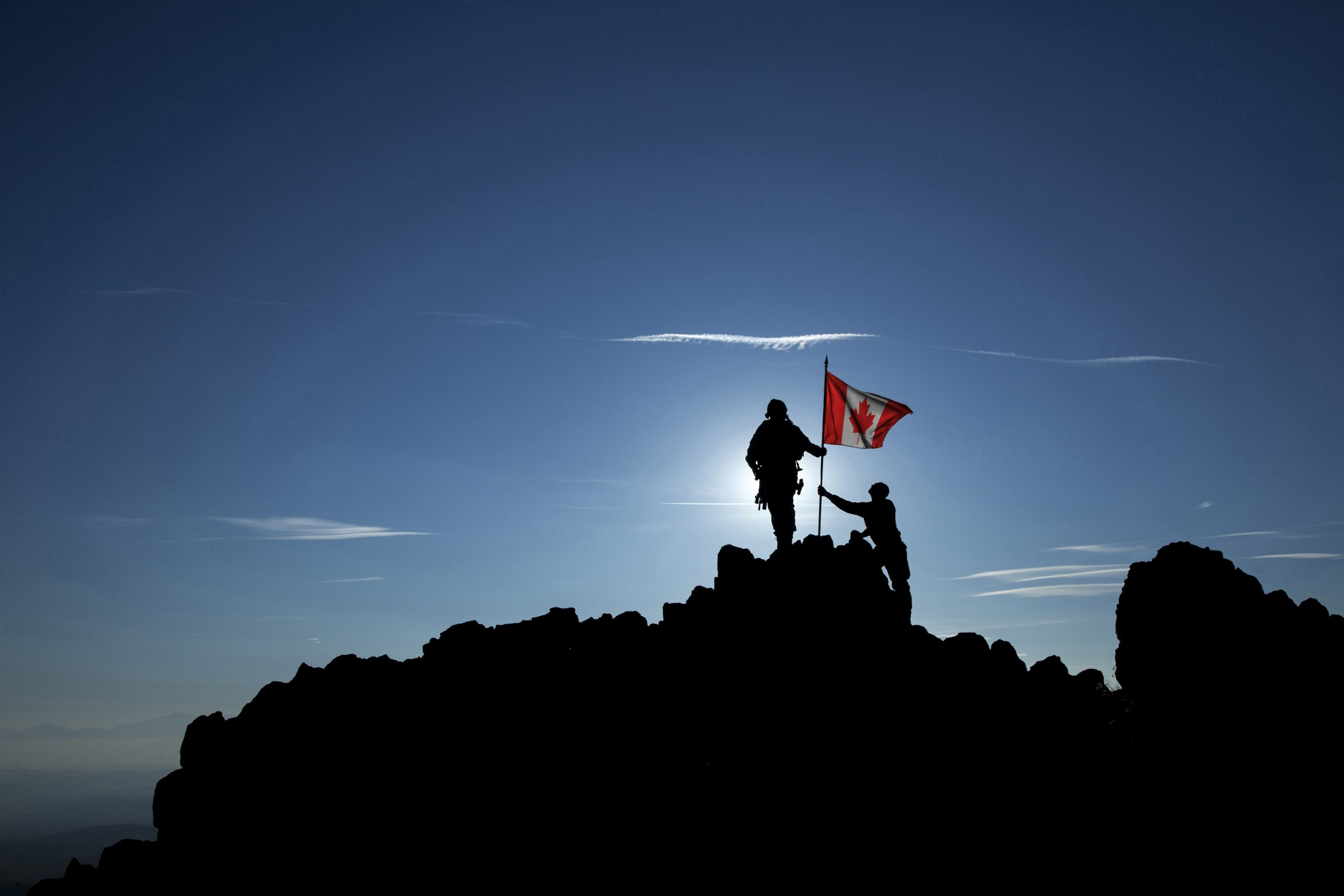 two canadian soldiers planting a flag